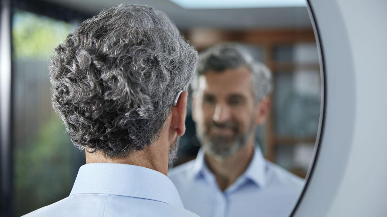 subtiel achter-het-oor hoortoestel man grijs middelbare leeftijd