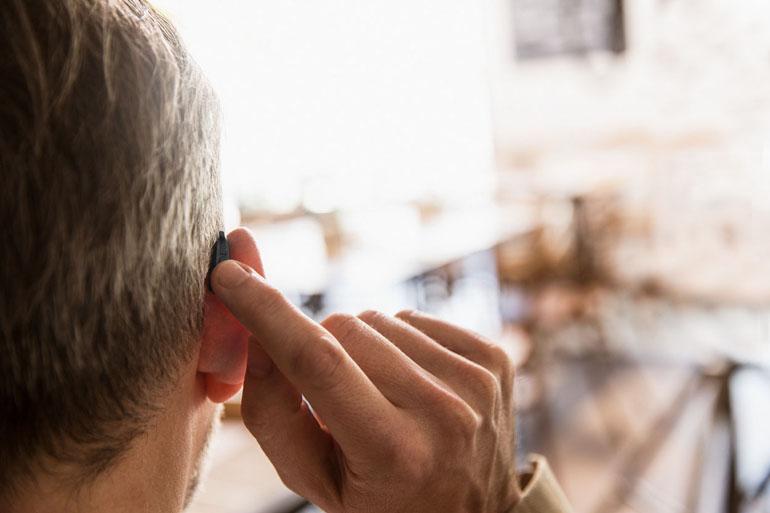 widex evoke manueel aanpassen hoorapparaat grijze man
